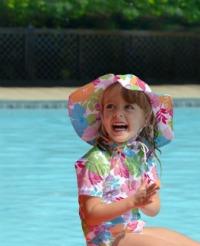 Little girl wearing iPlay cloth swim diaper and iPlay sun hat
